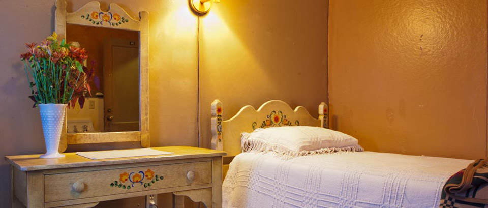 Interior shot of a Chateau guest room featuring a Montery furniture dressing table and bed