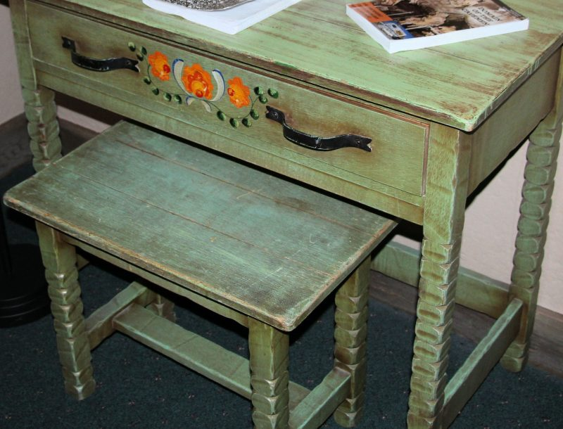 Detailed closeup of green Monterey furniture dressing table featuring floral decoration.